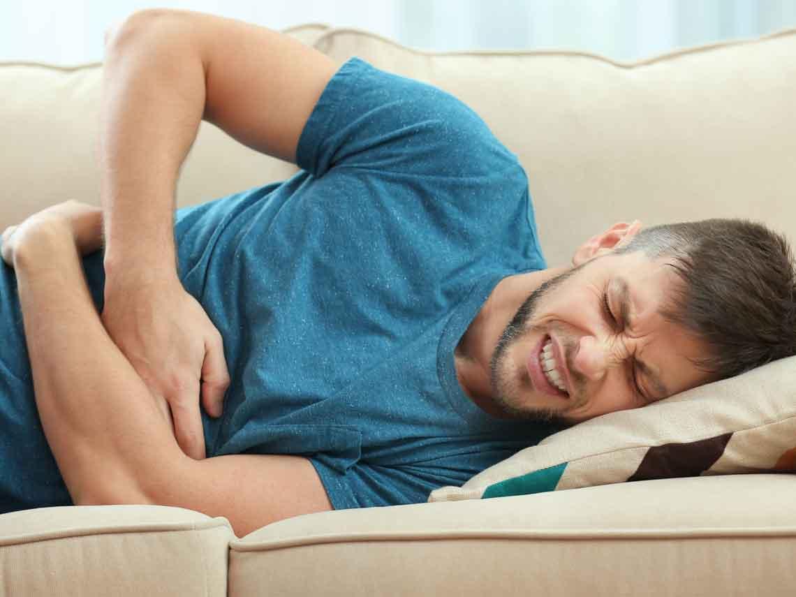 Hombre recostado con brazos en estómago